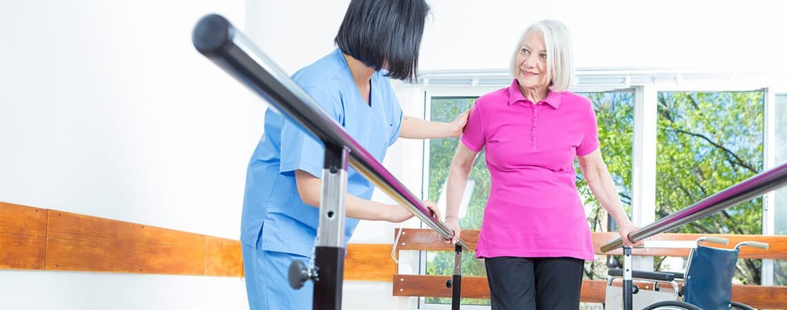 Older woman in a pink shirt holding support bars and receiving care from a rehabilitation professional